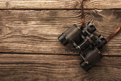 Binoculars on the wooden table. Top view horizontal Royalty Free Stock Image