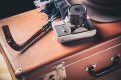 Binokel auf der Bootsstrichleiter auf Wasserhintergrund Alte Filmkamera mit Weinlesehut und -regenschirm auf altem braunem Koffer Lizenzfreies Stockbild