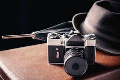 Binokel auf der Bootsstrichleiter auf Wasserhintergrund Alte Filmkamera mit Weinlesehut und -regenschirm auf altem braunem Koffer Lizenzfreies Stockfoto