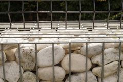 Bins filled with white pebbles. Close-up on a fragment of a fence made of gabions. royalty free stock image