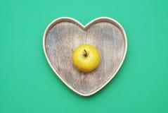 Bio äpple på wood hjärta Arkivfoto