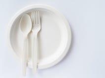 Bio colheres e forquilhas plásticas na placa de papel Imagens de Stock