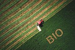 Bio- concetto e tactor che falciano campo verde immagini stock