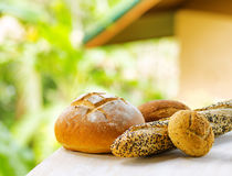 Fresh bread on white wooden table on rural landsca Stock Images
