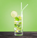 Glass of mojito cocktail on pastel green backgroun Stock Photos