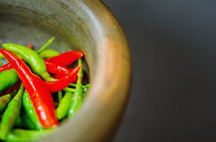 Red and green pepper in mortar Royalty Free Stock Photos