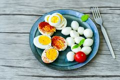 Hard Boiled Eggs. Bio Fresh hard boiled eggs ,mozzarella cheese and fresh basil sliced and broken with  onion and red pepper on wooden background Stock Photos