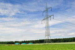 Bio fuel plant and power line. Power line aith bio fuel plant behind royalty free stock photo