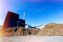 Bio fuel power plant. Bio power plant with storage of wooden fuel against blue sky Stock Photography
