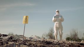 Bio-hazard, Hazmat scientists into Protective Coveralls shows sign think green on landfill with pointer biological stock footage