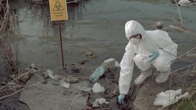 Bio-hazard in nature, hazmat chemist into protective suit taking infected water sample in test tubes for testing in. Bio-hazard in nature, hazmat chemist into stock video footage