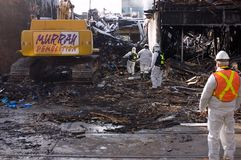 Bio-Hazardous Remains. Demolition crew equipped with bio-hazard suits and wearing autonomous breathing equipment are checking the charred remains of a building Royalty Free Stock Photography