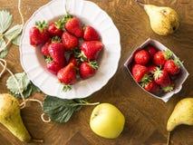 Bio jordgubbar med frukter på tabellen Arkivfoto