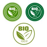 Bio labels with green leaves. Bio and natural food labels with text 100 percent, Bio and green leaves,  framed by round seals for food or beverage pack design Stock Images