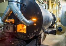 Burning bio pellets fuel in the boiler. Economical, ecologicla fuel. Bio pellets. Granulated wooden fuel. Economical, ecologicla fuel stock image