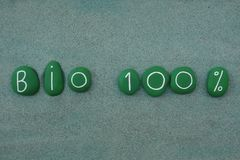 Bio 100 percent, green stones slogan over green sand. Slogan for bio one houndred percent composed with green colored stones over green sand Stock Illustration