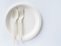 Bio plastic spoons and forks on paper plate. Bio plastic spoons and forks in biodegradable paper plate for one time use on white background Stock Images
