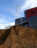 Bio power plant with storage of wooden fuel. Against blue sky Royalty Free Stock Photo