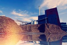 Bio power plant with storage of wooden fuel. Against blue sky Royalty Free Stock Images