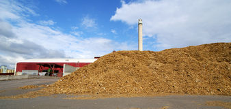 Bio power plant and storage of wooden fuel against blue sky Stock Photography