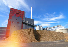 Bio power plant with storage of wooden fuel against blue sky Royalty Free Stock Photo