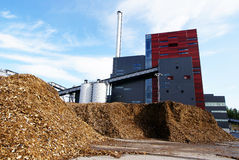 Bio power plant and storage of wooden fuel (biomass) against bl. Bio power plant with storage of wooden fuel (biomass) against blue sky Royalty Free Stock Image