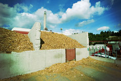 Bio power plant with storage wooden fuel (biomass) against bl Royalty Free Stock Photos