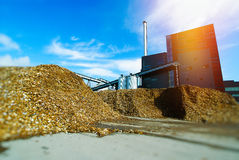Bio power plant with storage of wooden fuel biomass against bl. Ue sky Royalty Free Stock Photo