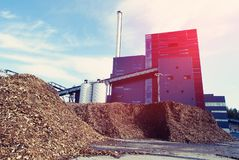 Bio power plant with storage of wooden fuel biomass. Against blue sky Royalty Free Stock Photo