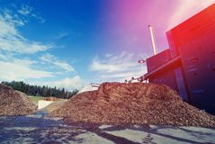 Bio power plant with storage of wooden fuel biomass. Against blue sky Stock Photos