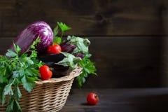 Bio purpere aubergines in een mand op houten achtergrond, lege ruimte voor tekst stock foto