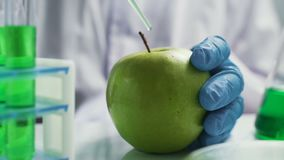 Bio scientist in gloves injects green solution or substance in genetically modified green apple in the laboratory
