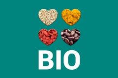 Bio- testo bianco sul fondo e sui cuori del turchese con i punti del cacao, grani bianchi della quinoa, bacche secche di goji e fotografie stock libere da diritti