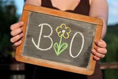 BIO written with flower. With chalk on slate shown by young female Stock Photo