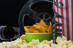 Biobegrepp av popcorn, chiper och gammalt videoband royaltyfri fotografi