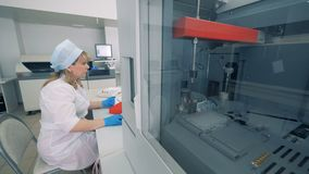 Biochemical analyzer is testing samples and a female worker is controlling the process