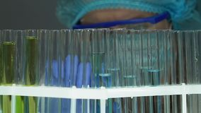 Biochemiker, der verschiedene Reagenzglasproben nach Experiment im Labor überprüft stock video