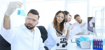 Biochemist with flask Petri sitting at a Desk Stock Images