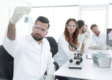 Biochemist with flask Petri sitting at a Desk Stock Photo