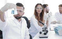 Biochemist with flask Petri sitting at a Desk Stock Image