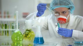 Biochemist pouring oily liquid in tube with blue substance and checking reaction