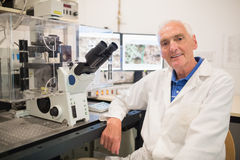 Biochemist using large microscope and computer Stock Photos