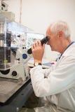 Biochemist using large microscope and computer Stock Photo