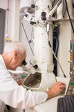 Biochemist using large microscope and computer Stock Photography