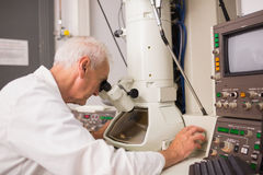 Biochemist using large microscope and computer Royalty Free Stock Photo
