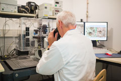 Biochemist using large microscope and computer Stock Images