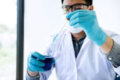 Biochemistry laboratory research, Scientist or medical in lab coat holding test tube with reagent with drop of color liquid over stock photography