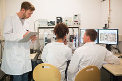 Biochemistry students using large microscope and computer Royalty Free Stock Photos