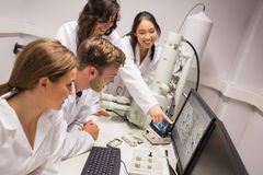 Biochemistry students using large microscope and computer Royalty Free Stock Images