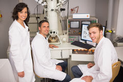 Biochemistry students using large microscope and computer Royalty Free Stock Photography